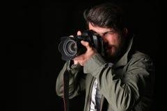 O fotógrafo no revestimento caqui toma a foto Fim acima Fundo preto Imagens de Stock