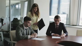 Сo-founders of the business take a counsel at the table. O-founders of the business take a counsel at the table. Secretary girl brings a folder with documents stock video footage