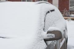 O fragmento de um carro sujo sob uma camada de neve durante a queda de neve pesada, carro é coberto com a neve, antes da limpeza  imagem de stock royalty free