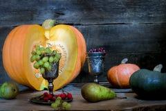 O frame dos presentes de abóboras de outono, de milho, de folhas da queda, de tomates, da airela vermelha da baga e da uva Fotografia de Stock Royalty Free