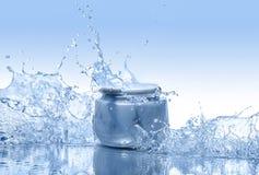 O frasco azul de estadas de creme hidratando na água espirra no fundo do azul do inclinação Fotografia de Stock