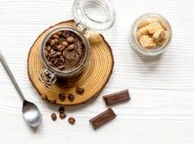 O frasco com corpo do café-chocolate esfrega o fundo de madeira da vista superior Imagem de Stock