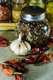 O frasco da pimenta e pimentão e alho inteiros da pimenta Foto de Stock
