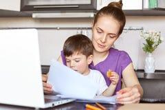 O freelancer da mãe em licenças de parto trabalha com documentação, faz o relatório comercial no laptop portátil, guarda o filho  Foto de Stock