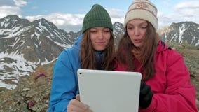 O freelancer das mulheres do turista usa um computador na natureza e senta-se na grama ao lado de uma tocha do gás As montanhas s video estoque