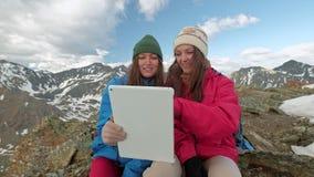 O freelancer das mulheres do turista usa um computador na natureza e senta-se na grama ao lado de uma tocha do gás As montanhas s filme