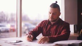 O freelancer do homem de negócios assina originais no café vídeos de arquivo