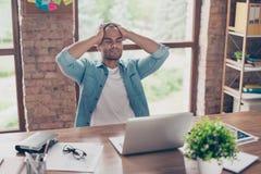 O freelancer doente forçado do mulato está tendo a dor de cabeça e está pensando como terminar seu trabalho Está em um esperto oc imagens de stock royalty free