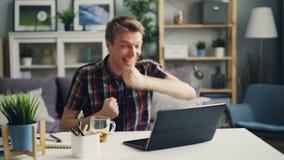 O freelancer excitado do homem está exultando sobre a gritaria bem sucedida do trabalho e está gesticulando olhando a tela do por filme