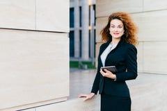 O freelancer fêmea bonito com cabelo leve luxuoso, olhos azuis, vermelho rouged os bordos e a pele pura, terno formal preto vesti imagem de stock