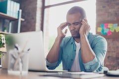 O freelancer forçado sobrecarregado do mulato está tendo a dor de cabeça e está pensando como terminar o projeto Está em um esper fotografia de stock royalty free