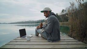 O Freelancer trabalha em seu portátil exterior ao lado do lago, sentando-se na lagoa video estoque