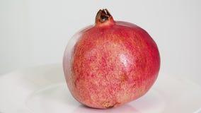 O fruto cor-de-rosa maduro inteiro da romã na placa branca gerencie filme