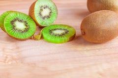 O fruto de quivi cortou em partes em um fundo de madeira Fotos de Stock Royalty Free