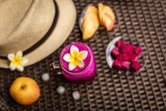 O fruto do dragão e o suco de maçã vermelhos em um vidro decorado com Plumeria florescem Chapéu, maçãs, fruto cortado do dragão,  Imagem de Stock Royalty Free