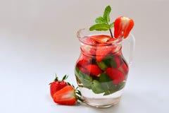 O fruto fresco do verão flavored infundiu a água da morango e da hortelã fotografia de stock