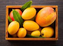 O fruto fresco e bonito da manga ajustou-se em uma caixa de madeira em um fundo de madeira escuro, espaço do spacetext da cópia Foto de Stock Royalty Free