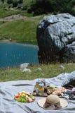 O fruto, a limonada e as pastelarias serviram em um piquenique contra a montanha fotos de stock royalty free