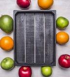 O fruto maduro fresco, maçãs das variedades diferentes, laranjas, manga apresentadas em torno de um lugar da caixa de madeira tex Foto de Stock