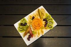 O fruto que corta em um branco plat foto de stock royalty free