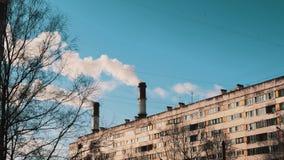 O fumo branco que sai conduz na área do dormitório da cidade no dia ensolarado do inverno filme