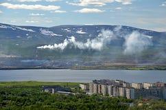 O fumo da tubulação da liga metalúrgica flui ao longo do lago para a cidade Foto de Stock Royalty Free