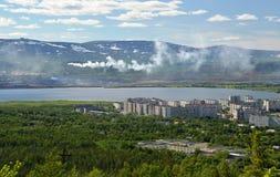 O fumo da tubulação da liga metalúrgica flui ao longo do lago para a cidade Imagem de Stock