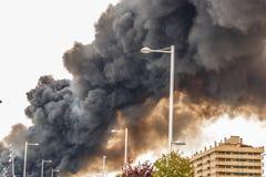 O fumo de um fogo enorme que inunda o céu de uma cidade Imagem de Stock Royalty Free