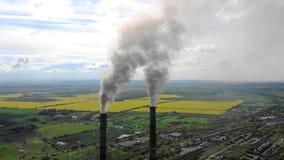 O fumo grosso denso de vista aérea vem das tubulações industriais contra o céu azul e a natureza vídeos de arquivo