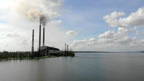 O fumo grosso denso de vista aérea vem das tubulações industriais contra o céu azul e a natureza e um grande lago video estoque