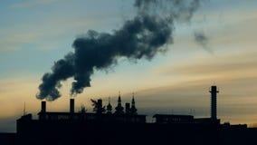 O fumo sai lentamente de diversas tubulações na fábrica contra o céu no por do sol Abóbadas da igreja no fundo video estoque