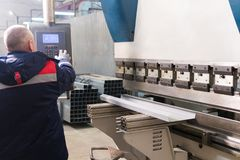 O funcionamento do operador cortou e folha de metal de dobra pela máquina de dobra da folha de metal da elevada precisão, folha d Imagens de Stock