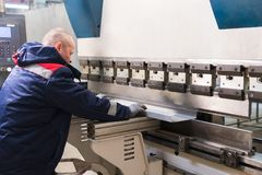 O funcionamento do operador cortou e folha de metal de dobra pela máquina de dobra da folha de metal da elevada precisão, folha d Imagens de Stock Royalty Free