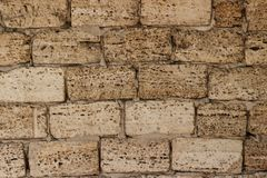 O fundo é uma parede amarela de grandes tijolos do arenito do coquina selou blocos dos escudos foto de stock