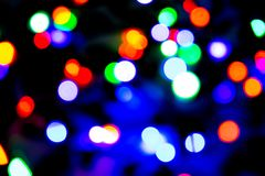 O fundo borrado com luzes coloridas do bokeh no fundo roxo e azul escuro/borrou luzes de Natal Fotografia de Stock