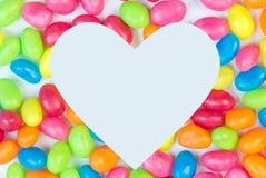 O fundo colorido do feijão de geleia com coração branco deu forma ao espaço para fotos de stock royalty free