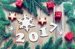 O fundo 2017 com 2017 figuras, Natal do ano novo brinca, vida ramo-nova do ano 2017 do abeto ainda Fotografia de Stock