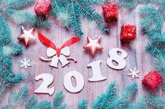 O fundo 2018 com 2017 figuras, Natal do ano novo feliz brinca, ramos de árvore azuis do abeto Composição 2018 do ano novo Foto de Stock Royalty Free