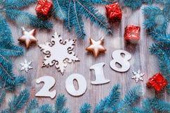O fundo 2018 com 2017 figuras, Natal do ano novo feliz brinca, ramos de árvore azuis do abeto Composição 2018 do ano novo Imagem de Stock Royalty Free
