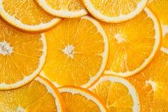O fundo cortado das laranjas, fruto fresco brilhante cortou mesmo em fatias Foto de Stock Royalty Free