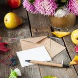 O fundo da ação de graças com frutos sazonais, as flores, o cartão e poucos craft envelopes em uma tabela de madeira rústica Harv Foto de Stock