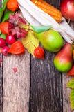 O fundo da ação de graças com outono frutifica e sae em uma tabela de madeira rústica Opinião superior da colheita do outono Copi Imagem de Stock