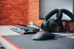 O fundo da arena do jogo com o computador dos fones de ouvido da engrenagem do rato, focuse em fones de ouvido selecionou o focus fotografia de stock