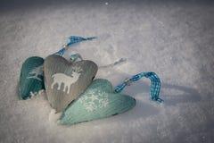 O fundo da neve com três corações com um inverno à moda imprime Fotografia de Stock Royalty Free