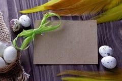 O fundo da Páscoa com amarelo de pano de serapilheira dos ovos da páscoa empluma-se a fita e o espaço verdes para o texto Foto de Stock