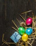 O fundo da Páscoa com galinha colorida eggs em placas cinzentas idosas Fotografia de Stock Royalty Free