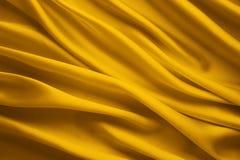 O fundo da tela de seda, pano amarelo do cetim acena folhas foto de stock