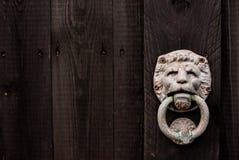 O fundo de madeira do preto escuro com leão deu forma à aldrava de porta e ao s fotografia de stock