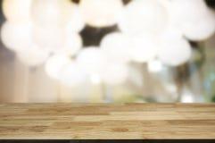 O fundo de madeira marrom vazio da tabela e do borrão do sumário de luzes do restaurante pode ser usado para a montagem ou indica fotos de stock