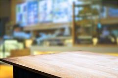 O fundo de madeira marrom vazio da tabela e do borrão do sumário de luzes do restaurante pode ser usado para a montagem ou indica imagem de stock royalty free